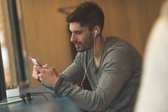 Uomo alla moda che lavora al suo telefono nella caffetteria fotografia stock libera da diritti