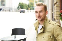 Uomo alla moda che si siede all'aperto Fotografia Stock