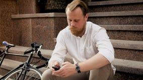 Uomo alla moda con la barba che si rilassa sulla via e sul messaggio di battitura a macchina sullo Smart Phone Fotografia Stock Libera da Diritti