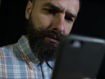 Uomo alla moda con una barba e sguardi dei baffi ad un telefono cellulare con un'espressione facciale seria su un fondo nero immagini stock