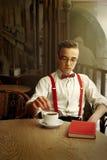 Uomo alla moda dei pantaloni a vita bassa che si siede in caffè con caffè ed il libro in vecchio Immagine Stock
