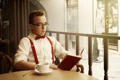 Uomo alla moda dei pantaloni a vita bassa che si siede in caffè con caffè ed il libro in vecchio Fotografia Stock Libera da Diritti