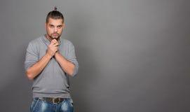 Uomo alla moda dei pantaloni a vita bassa con messo le mani in studio Fotografia Stock