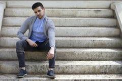 Uomo alla moda in maglione con la barba che si siede sulle scale immagini stock libere da diritti