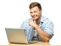 Uomo alla moda sorridente dietro il computer portatile Fotografia Stock Libera da Diritti