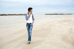 Uomo alla moda sul telefono e camminare sulla spiaggia Immagine Stock