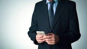 Uomo alla moda in vestito facendo uso del telefono guarda elegante Uomo d'affari archivi video