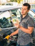 Uomo alla stazione di benzina che si occupa dei soldi per i prezzi in aumento Immagine Stock
