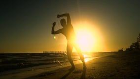 Uomo allegro che balla sulla spiaggia Salta al sole L'uomo sta divertendosi È felice Siluetta di un uomo a stock footage