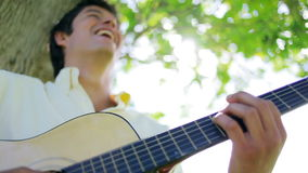 Uomo allegro che gioca la chitarra video d archivio
