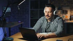 Uomo allegro che gode della musica in cuffie e che lavora con il computer portatile in ufficio scuro stock footage