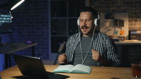 Uomo allegro che gode della musica in cuffie occupate con ballare di computer portatile nell'ufficio scuro stock footage