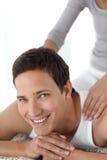 Uomo allegro che gode di un massaggio posteriore dalla sua moglie Fotografia Stock