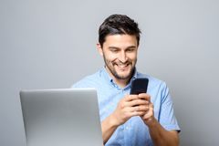 Uomo allegro che per mezzo del cellulare e sedendosi alla tavola con il computer portatile Fotografie Stock