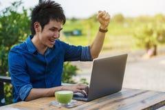 Uomo allegro che per mezzo del computer portatile fotografia stock libera da diritti