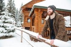 Uomo allegro che sta davanti al cottage di legno all'inverno Fotografie Stock Libere da Diritti