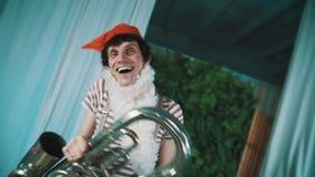 Uomo allegro in costume nano che imbroglia intorno con la tuba tagliata stancata della latta in mani stock footage