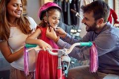 Uomo allegro e bicicletta e caschi nuovi di compera della donna per la bambina nel negozio della bici fotografia stock libera da diritti