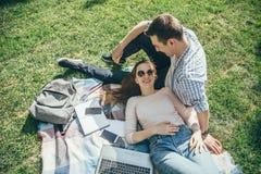 Uomo allegro e donna che riposano in natura dopo l'apprendimento fotografie stock libere da diritti