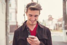Uomo allegro facendo uso del cellulare all'aperto fotografia stock