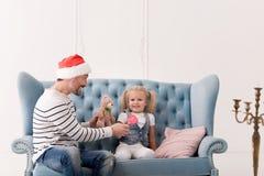 Uomo allegro felice che dà una lecca-lecca a sua figlia Fotografia Stock
