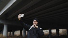 Uomo allegro felice che prende il ritratto del selfie con lo smartphone dopo la formazione nella posizione urbana di aria aperta  Fotografia Stock