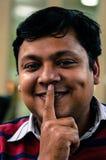 Uomo allegro indiano che fa un'espressione per tacere immagine stock libera da diritti