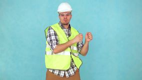 Uomo allegro in un'uniforme della costruzione ed in un casco bianco, ballanti video d archivio
