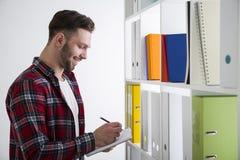 Uomo allegro in una scrittura delle biblioteche Immagini Stock