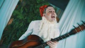 Uomo allegro vestito come dancing nano barbuto con la chitarra acustica in mani archivi video