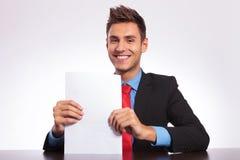 Uomo allo scrittorio che mostra alcuni documenti Immagine Stock