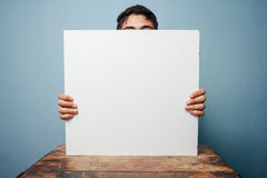 Uomo allo scrittorio che si nasconde dietro un bordo bianco fotografie stock