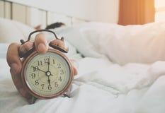 Uomo allungato a letto dopo le 6 DI MATTINA della sveglia Immagine Stock Libera da Diritti