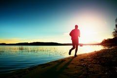 Uomo alto in abiti sportivi al tramonto stupefacente nello sport e nell'allenamento di addestramento di stile di vita del paese t Immagine Stock