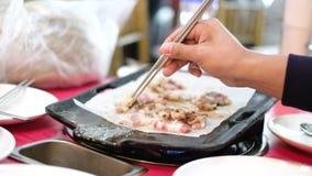 Uomo alto vicino che griglia bacon e carne sul tavolo da pranzo sudicio nel ristorante archivi video