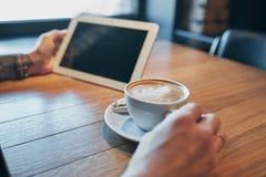 Uomo alto vicino delle mani facendo uso della compressa, wifi di collegamento Lavorando appena dal caffè Schermo nero immagini stock libere da diritti