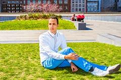 Uomo americano che si rilassa sul prato inglese verde a New York Immagini Stock Libere da Diritti