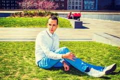 Uomo americano che si rilassa sul prato inglese verde a New York Fotografie Stock