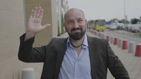 Uomo amichevole in vestito che ondeggia la sua mano che dice ciao con il sorriso sicuro positivo sulla via pubblica della città - stock footage