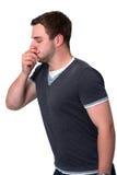 Uomo ammalato che tossisce in è mano Fotografie Stock