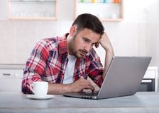Uomo annoiato che esamina computer portatile Fotografia Stock Libera da Diritti