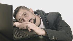 Uomo annoiato di affari che scrive al suo scrittorio stock footage