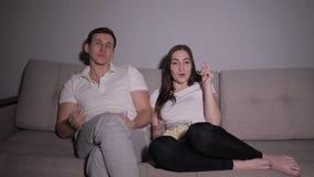 Uomo annoiato e donna sorridente che si siedono su un sofà alla notte che guarda TV stock footage