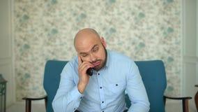 Uomo annoiato sul sofà che guarda TV a casa archivi video