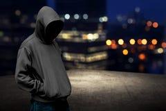 Uomo anonimo in cappuccio sul tetto Immagine Stock