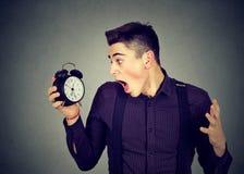 Uomo ansioso che esamina sveglia Concetto di pressione di tempo fotografie stock