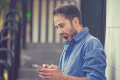 Uomo ansioso che esamina telefono che vede cattivo messaggio o foto con emozione disgustosa sul fronte Fotografie Stock