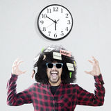 Uomo ansioso di afro con l'orologio di parete Fotografia Stock
