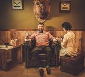 Uomo antiquato sicuro con vetro di whiskey che fa manicure maschio in un negozio di barbiere fotografie stock libere da diritti
