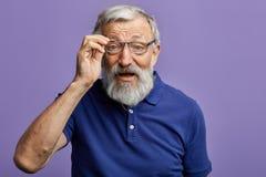 Uomo anziano allegro che esamina attraverso i vetri la macchina fotografica fotografia stock libera da diritti